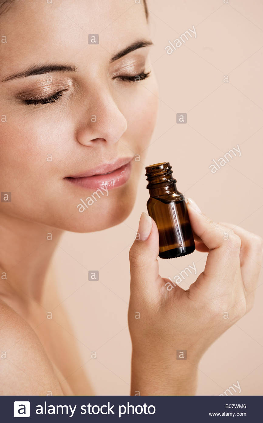 Woman smelling a bottle of essential oil - Stock Image