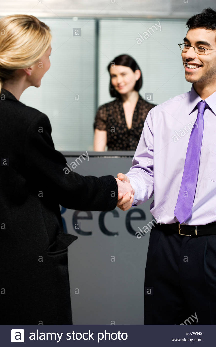 Businesswoman being greeted at office reception - Stock Image