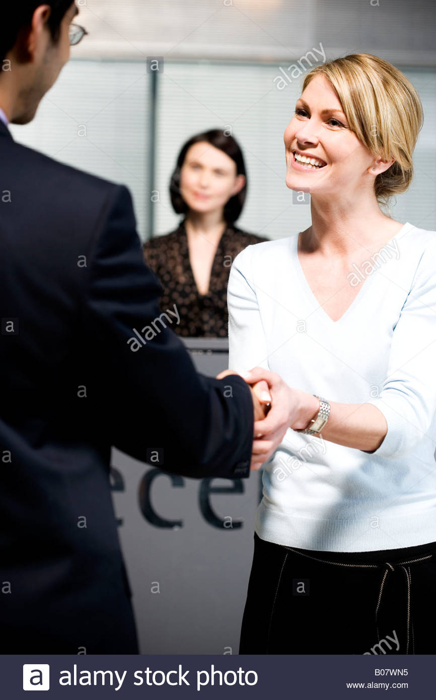 Businessman being greeted at office reception - Stock Image