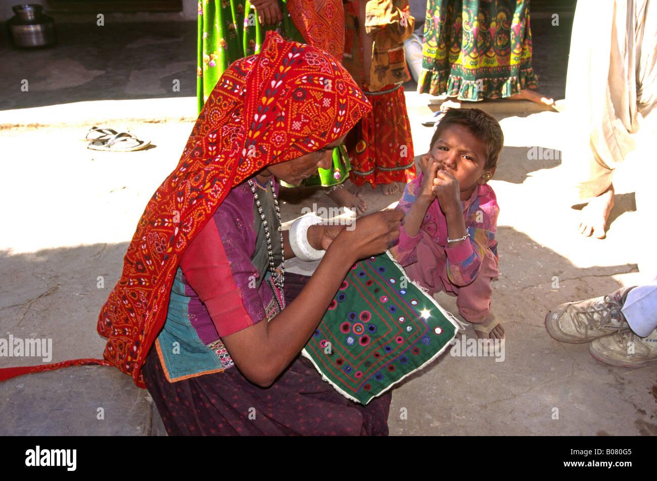 India Gujerat Rann of Kutch crafts Satapar Village Ahir woman sewing shisha mirror work cushion cover - Stock Image