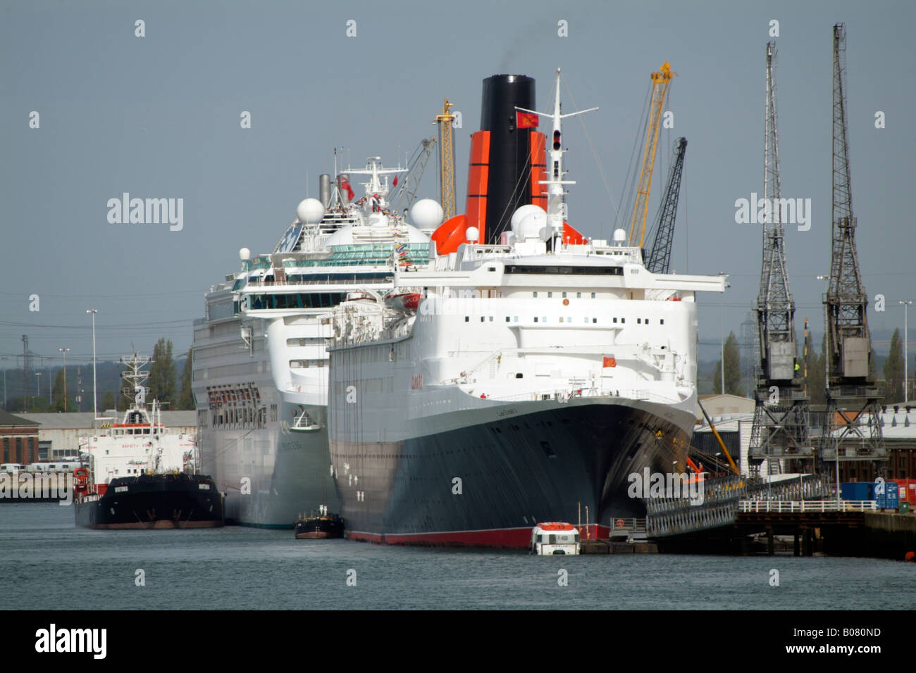 QE2 about to depart on her final cruise Old and new Cruise ships Southampton Port southern England UK - Stock Image