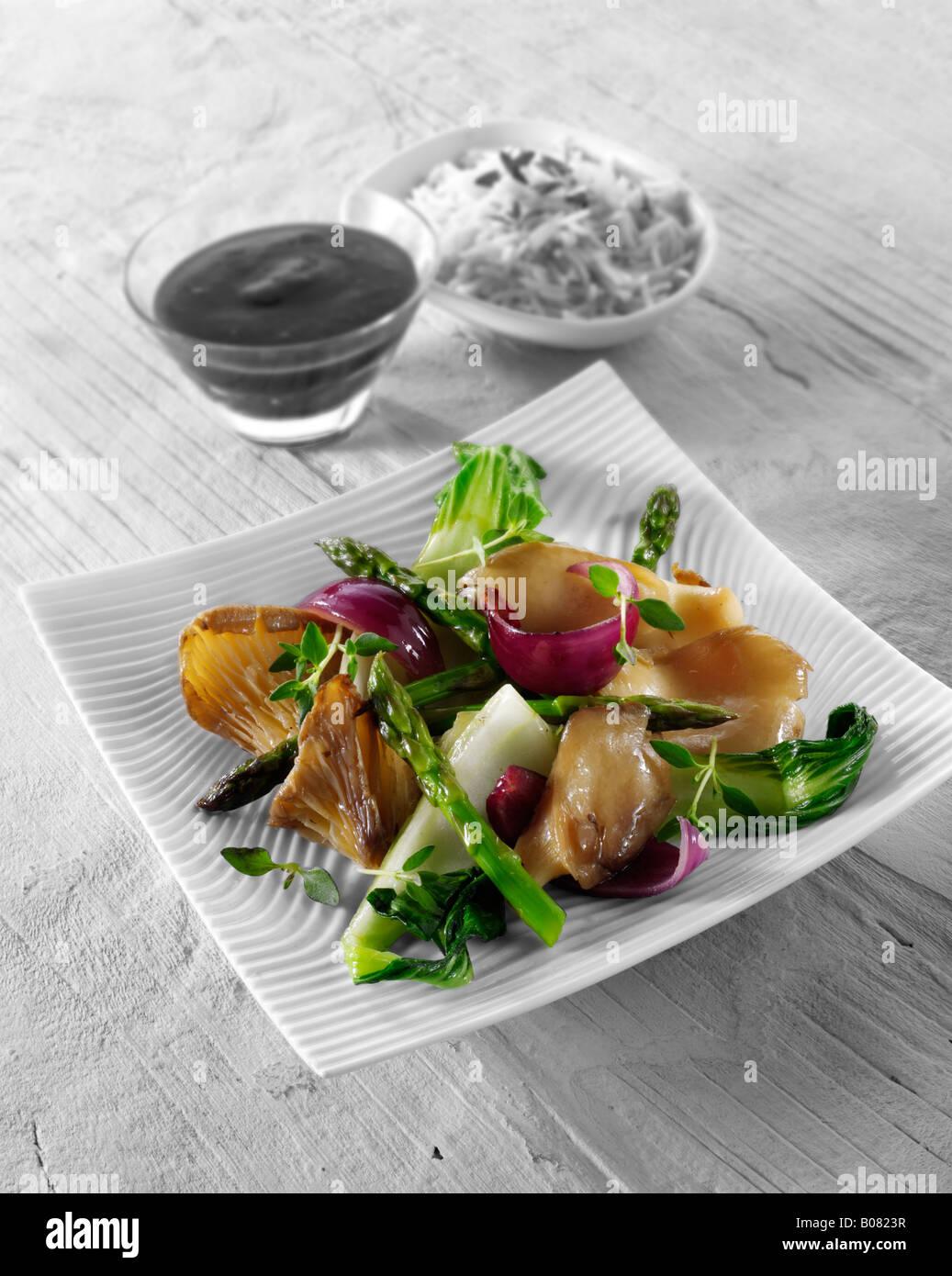 Oriental vegetarian stir fry of vegetables with pak choi, asparagus, mnushrooms and hoisin sauce - Stock Image