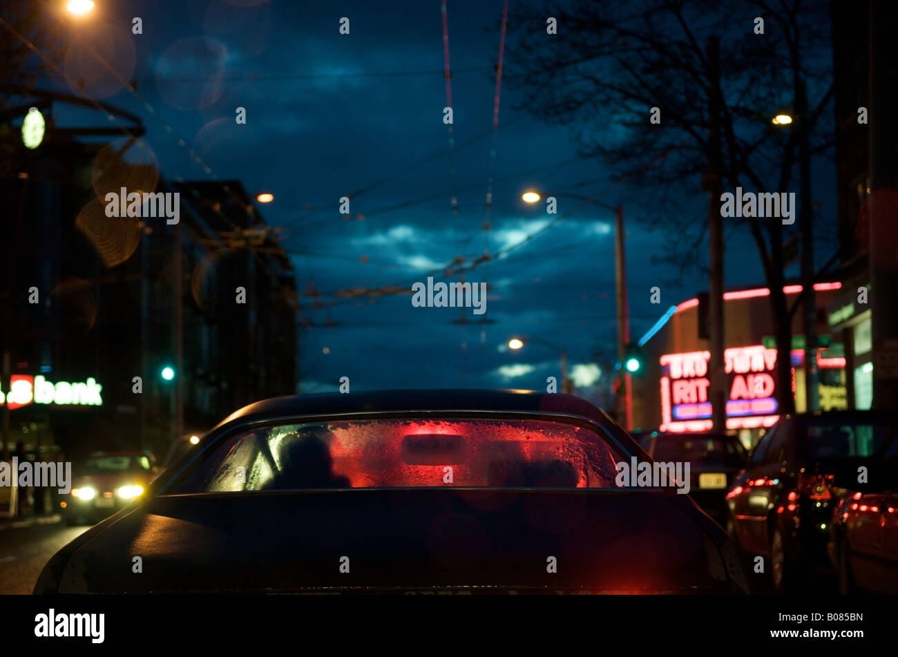 View of red brake lights through the rear window of a car on a rainy evening in Seattle, WA, USA. - Stock Image