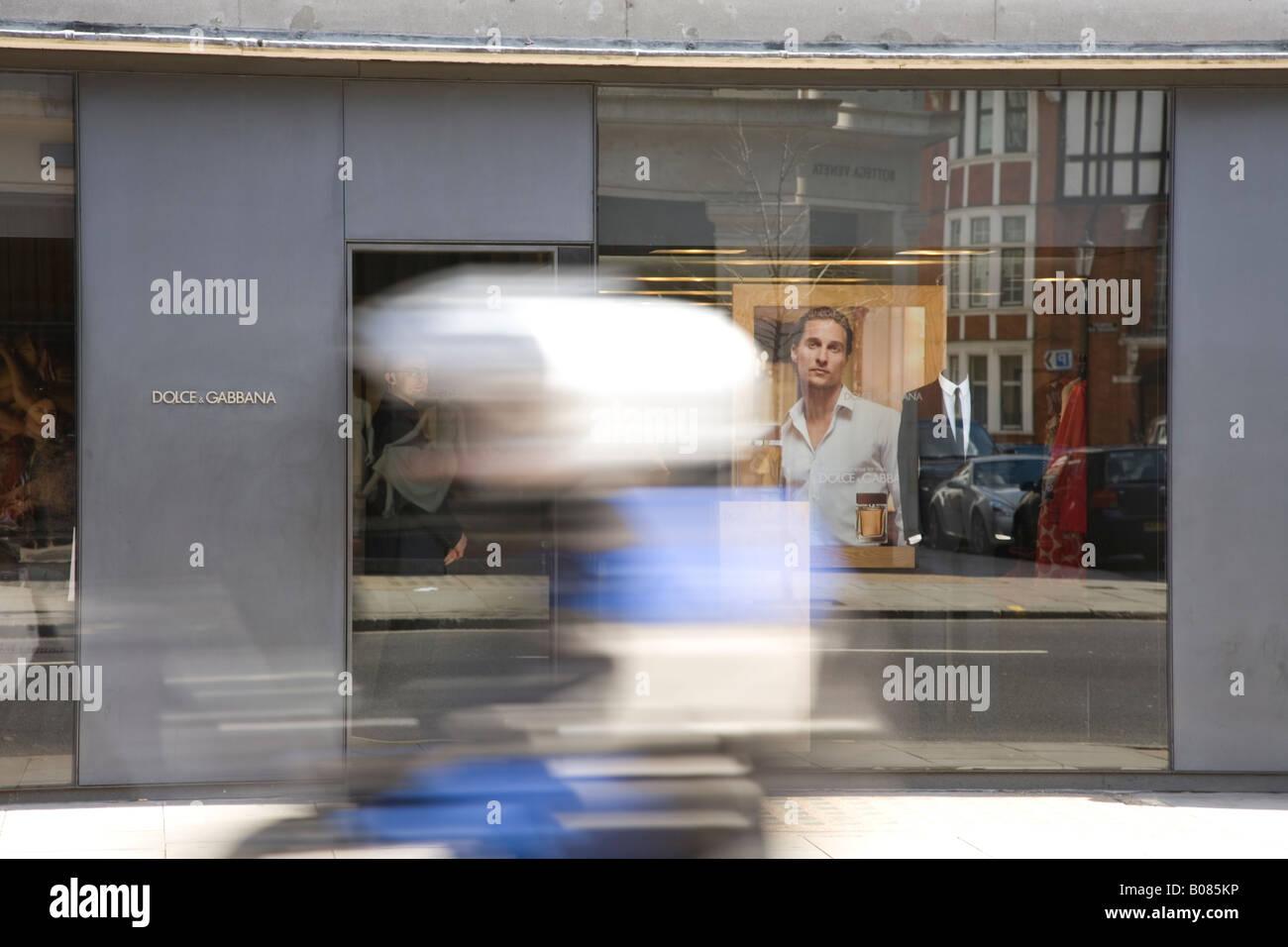 Motorbike rides past dolce and gabanna Shop Upper Sloane Street Knightsbridge - Stock Image