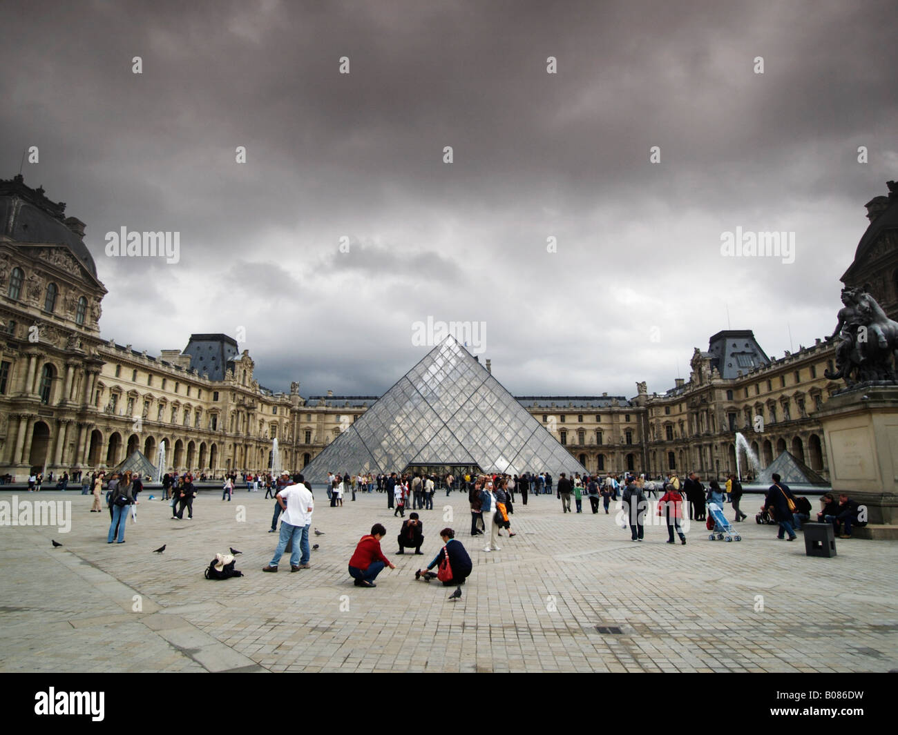 Louvre courtyard with many people tourists and the pyramid by I M Pei Paris France - Stock Image