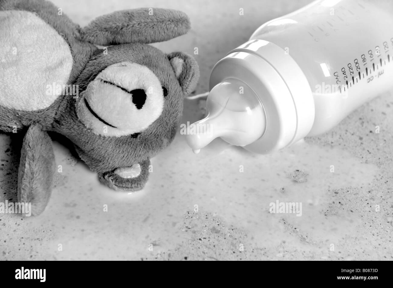 a teddy bear and a spilt bottle of baby milk - Stock Image