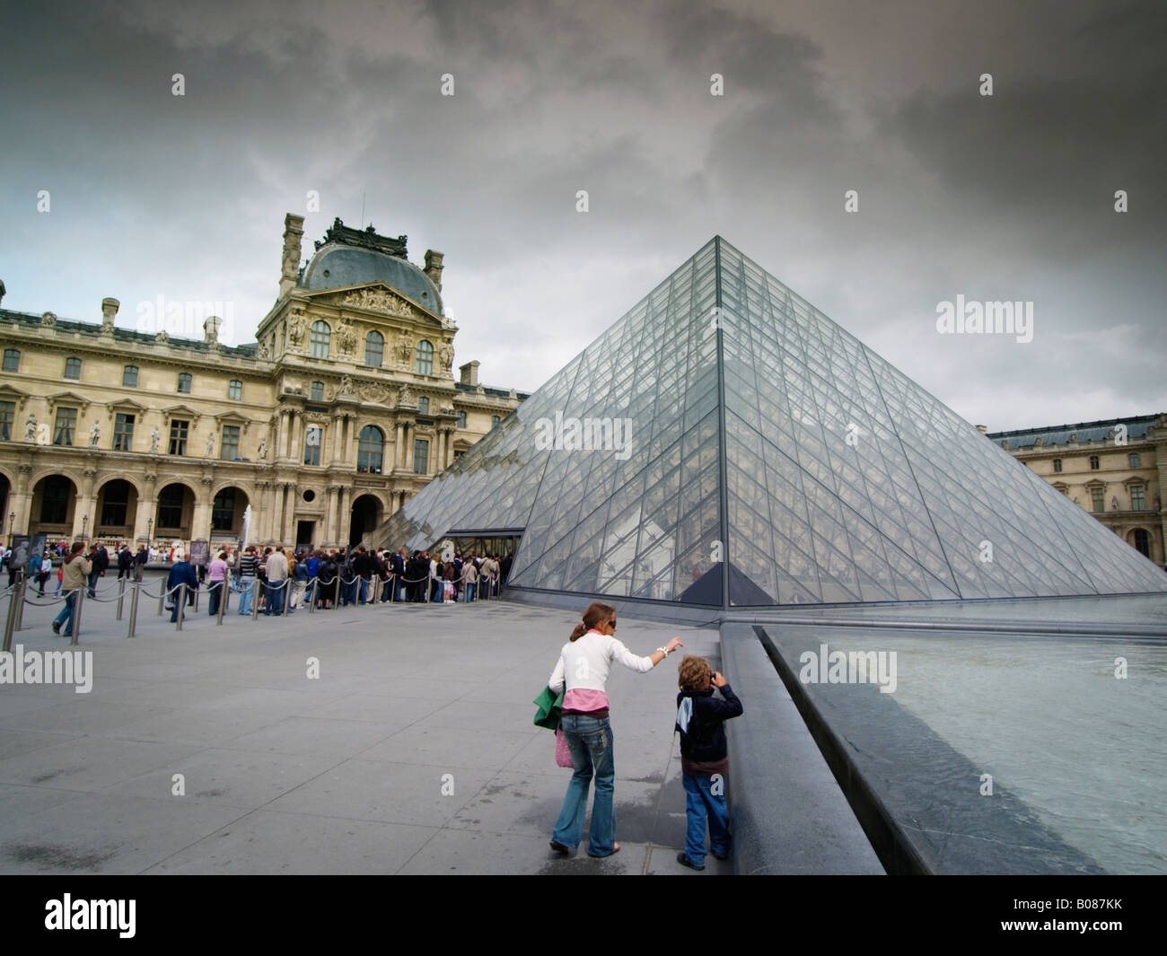 The Pyramid by architect I M Pei at the Louvre museum in Paris France with queue at the museum entrance - Stock Image