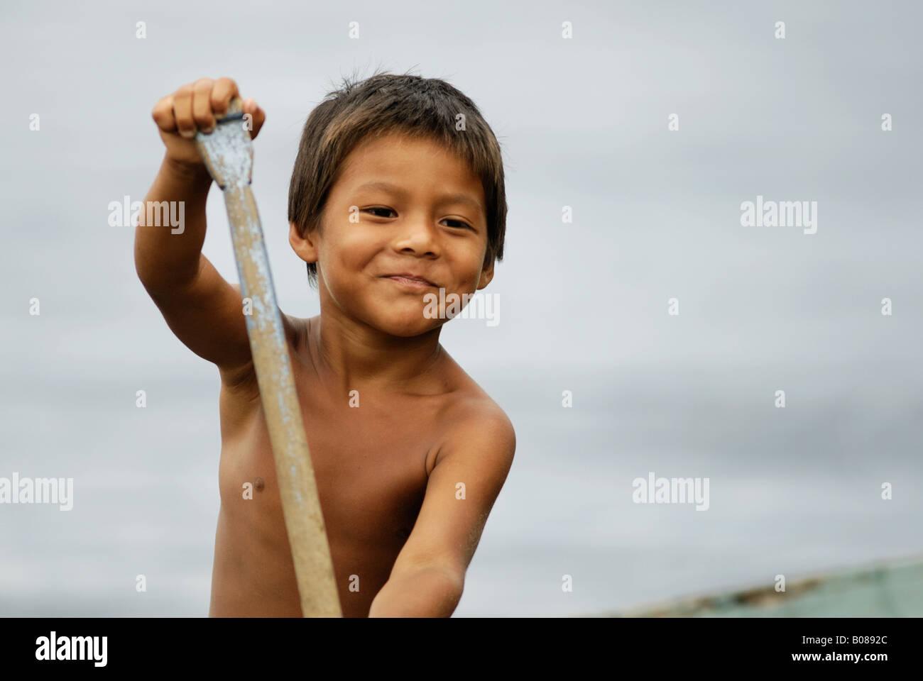Native Amazon boy paddling a canoe - Stock Image