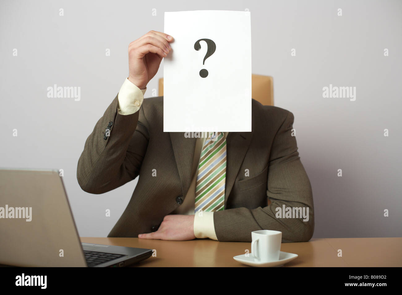 Question mark on a sheet of paper covering businessman's face - Stock Image