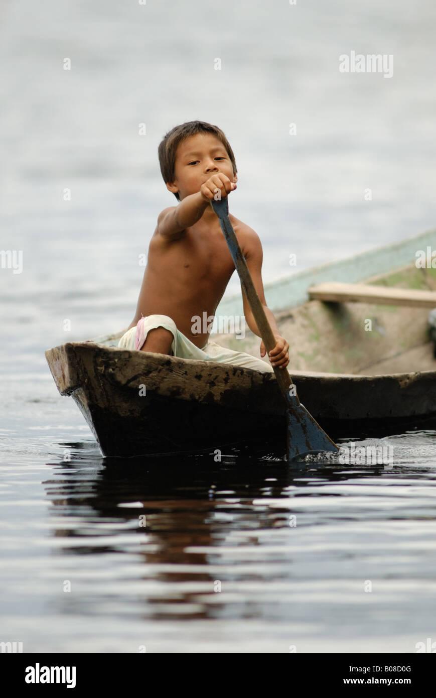 Boy from the Amazon paddling a canoe - Stock Image