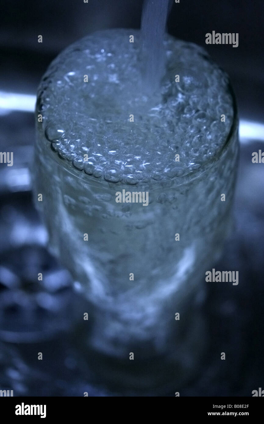 A vertical shot of a glass filling up with water. Stock Photo