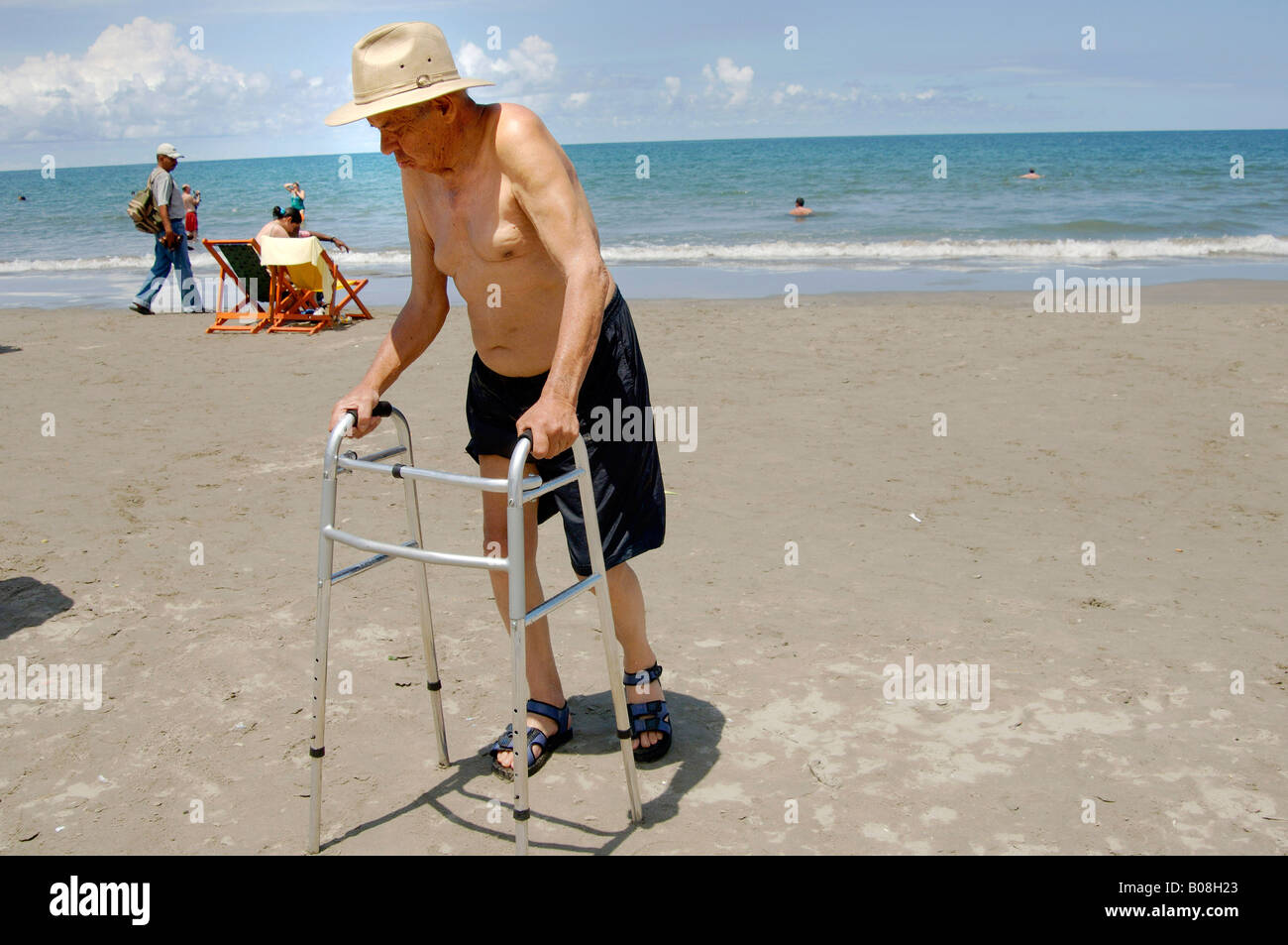 Senior man at the beach with a walker - Stock Image