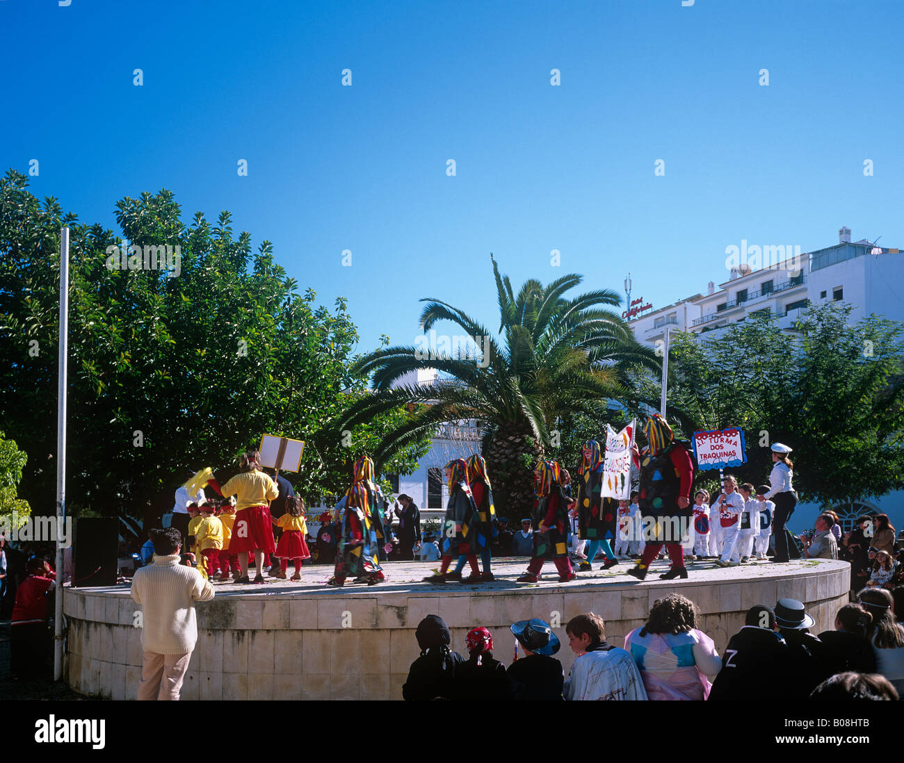 Costumed figures dancing in the central plaza of Albufeira early Febuary at the start of Lent Algarve southern Portugal - Stock Image