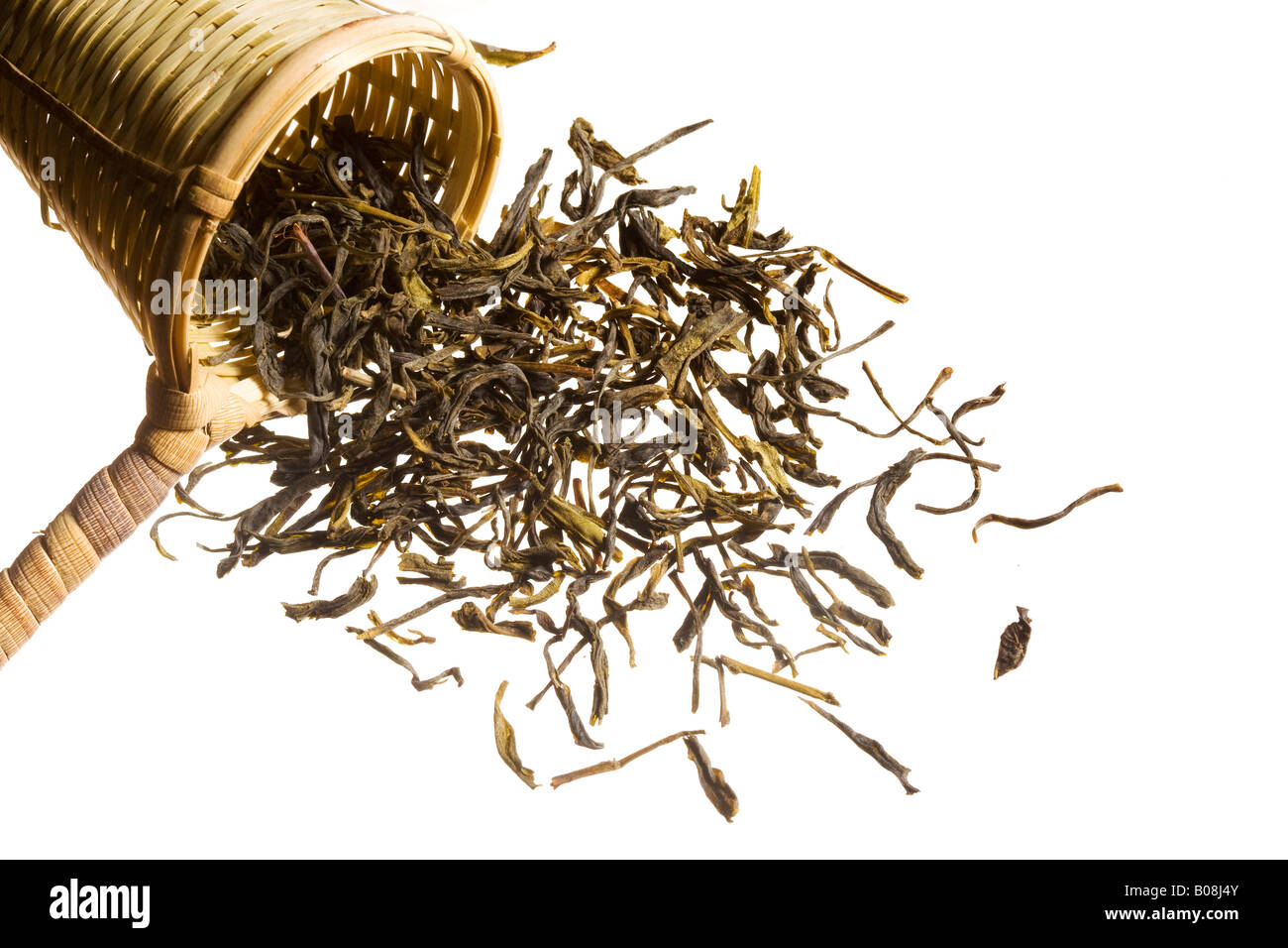 An overflowing heap of raw tea spilling out of a woven scooper. - Stock Image