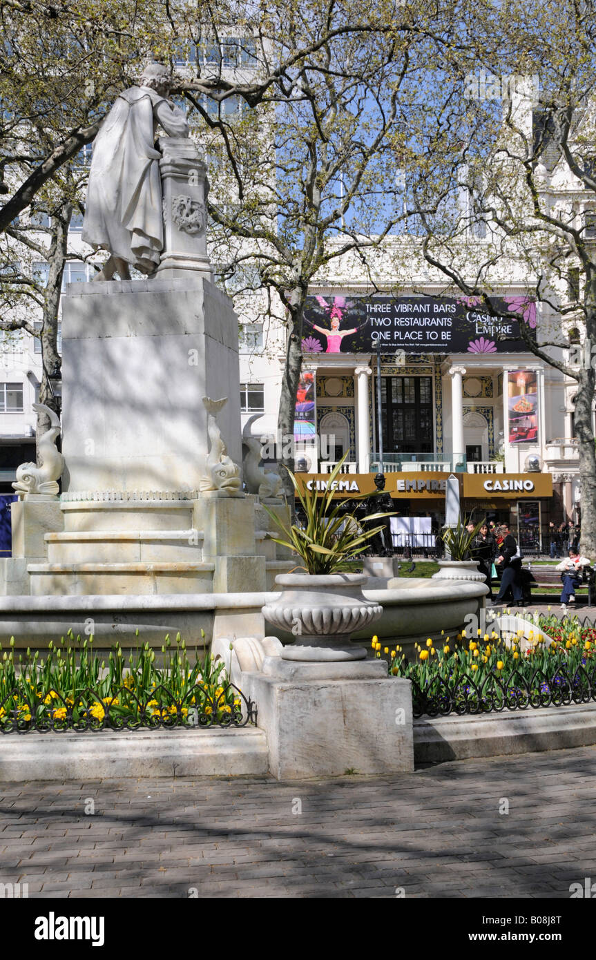 Gardens and statue in Leicester Square West End London Empire cinema and casino beyond - Stock Image