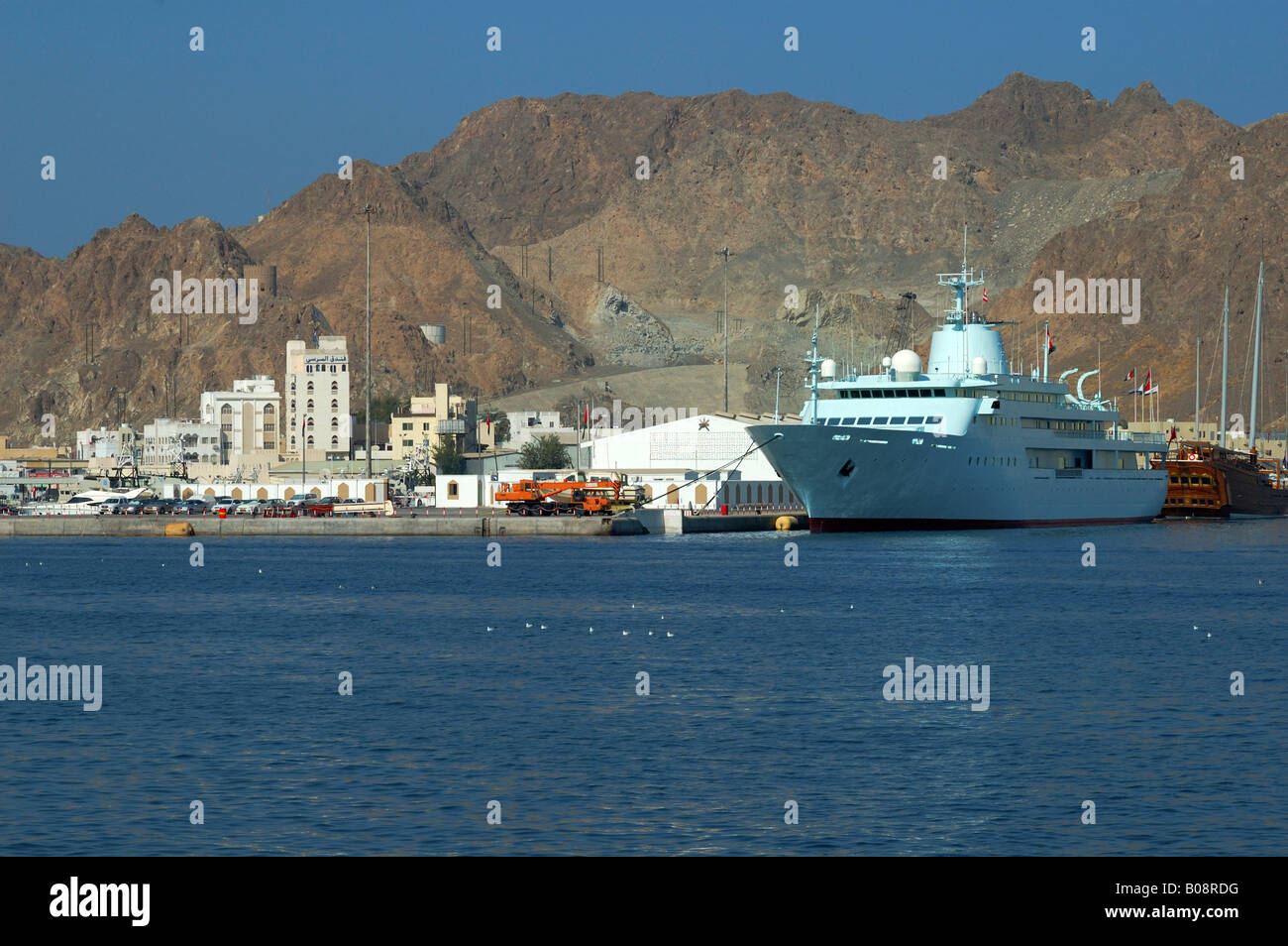 Large motor yacht in the harbour with rocky mountains rising at back, Muttrah, Muscat, Sultanate of Oman, Middle Stock Photo