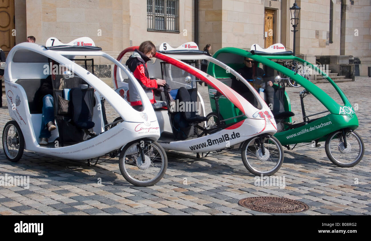 Bicycle rickshaw taxis parked on a cobblestone street in Dresden, Saxony, Germany Stock Photo