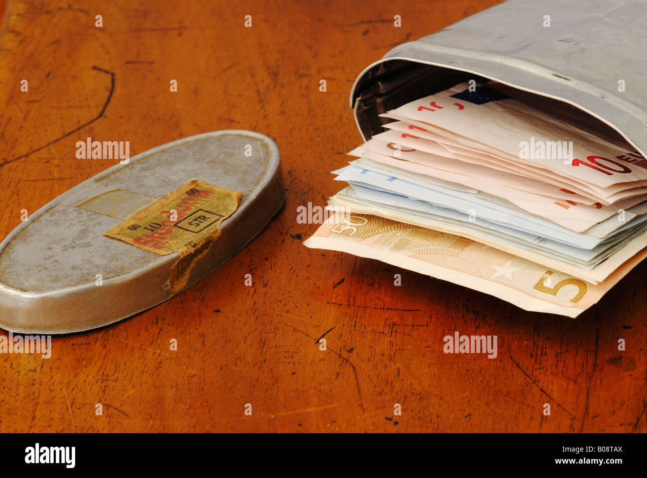 Old silver tin, patina, filled with Euro bills - Stock Image