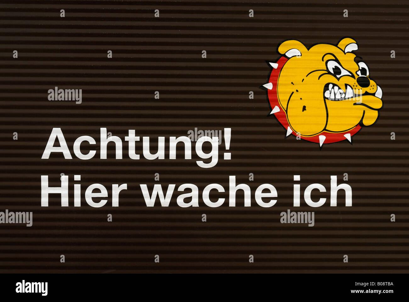 Garage door with a sign: 'Achtung, hier wache ich' (Beware of Dog) - Stock Image
