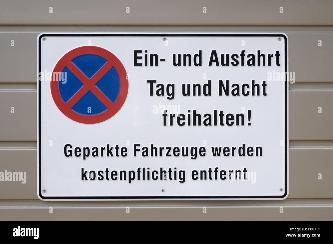 No parking sign, 'Ein- und Ausfahrt Tag und Nacht freihalten! Geparkte Fahrzeuge werden kostenpflichtig abgeschleppt' - Stock Image