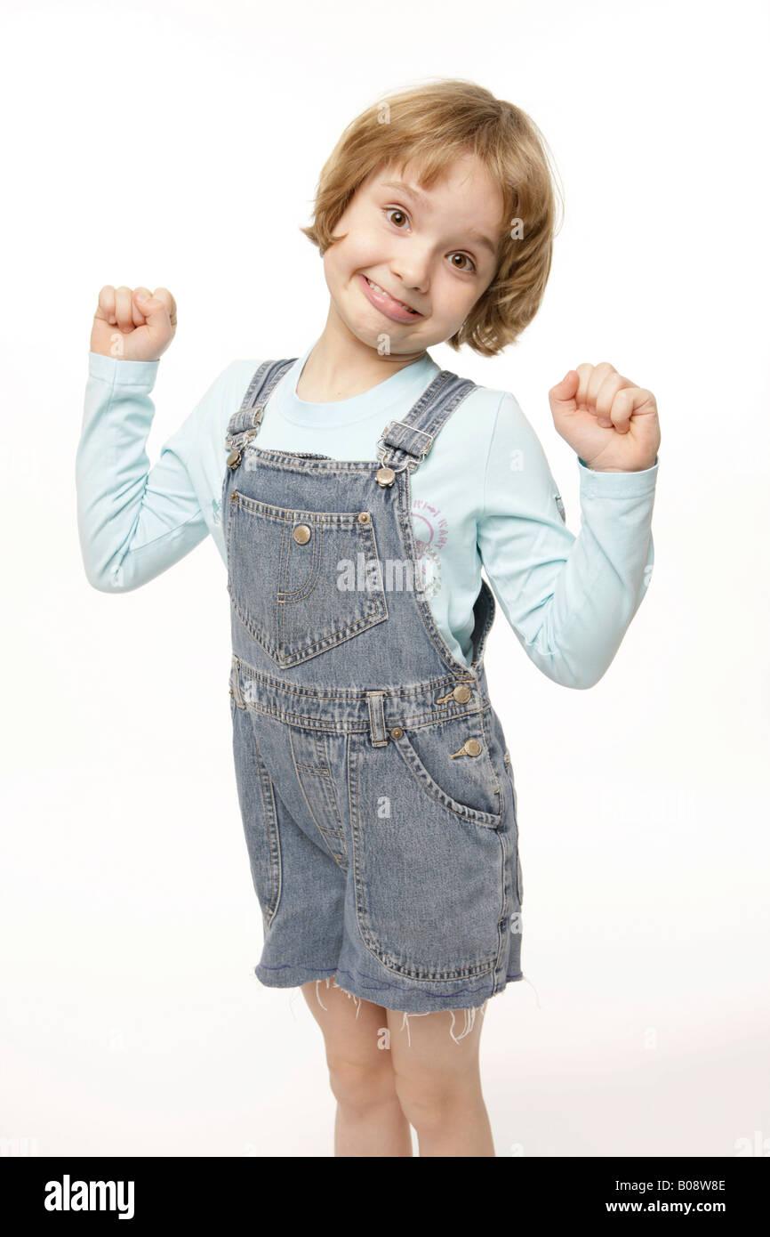 Dark-blonde, 8-year-old girl acting goofy, winner's pose - Stock Image
