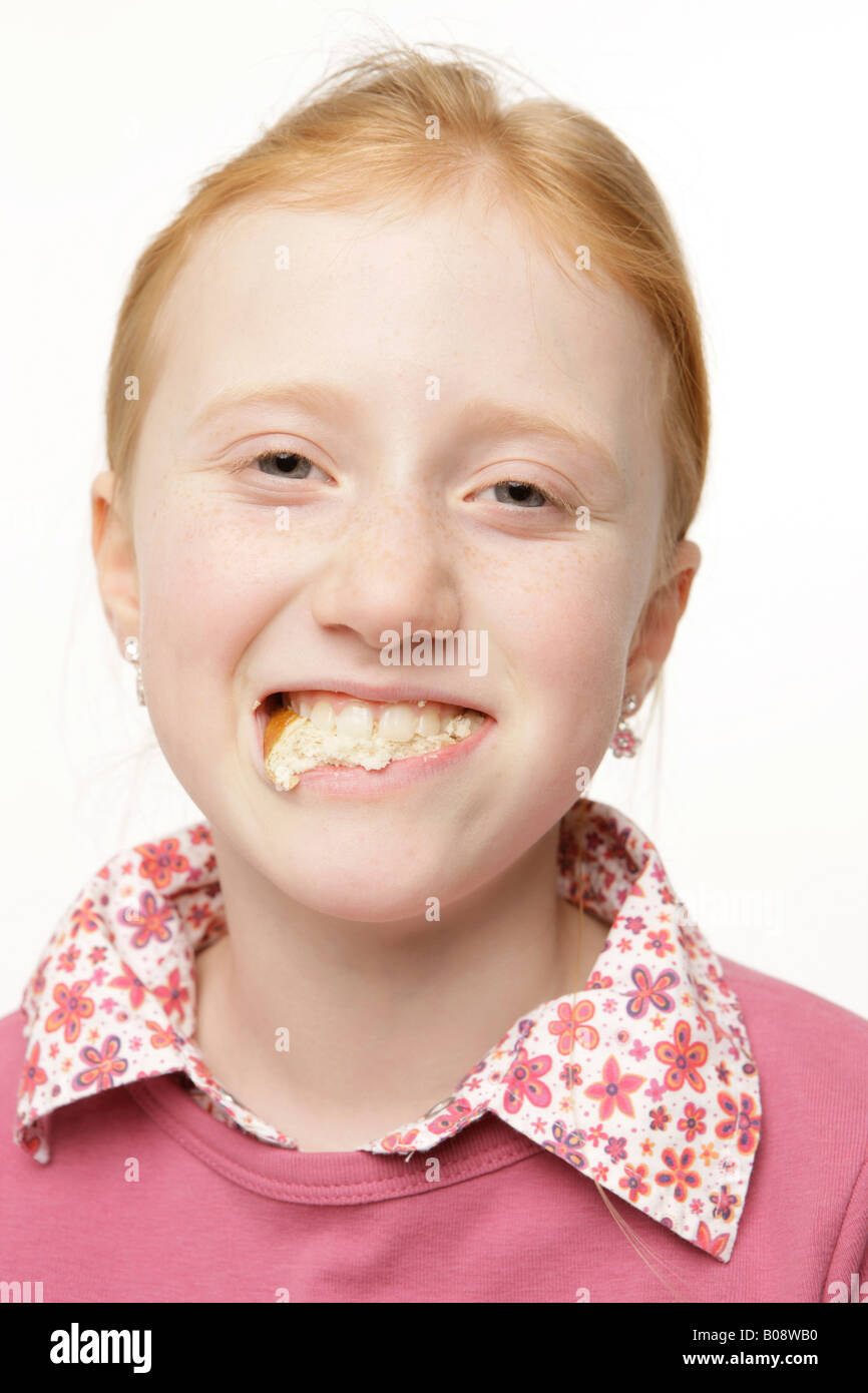 8-year-old red-haired girl with bread in her mouth Stock Photo