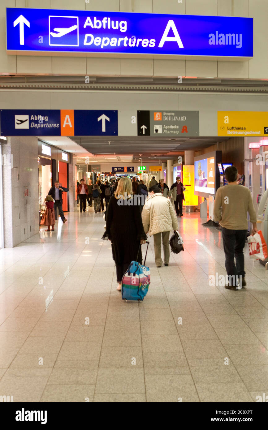 Passenger pulling her carry-on luggage to her departure gate, Frankfurt International Airport, Hesse, Germany - Stock Image