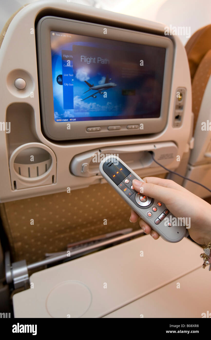 Using the remote control to operate the economy class entertainment program on board a Singapore Airlines Boeing - Stock Image