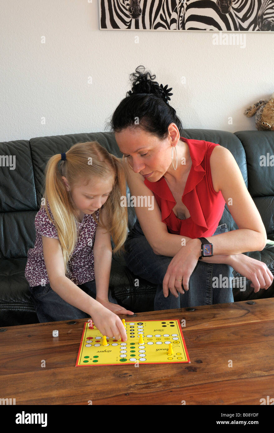 Mother with child, 10 years old, playing Ludo board game Stock Photo