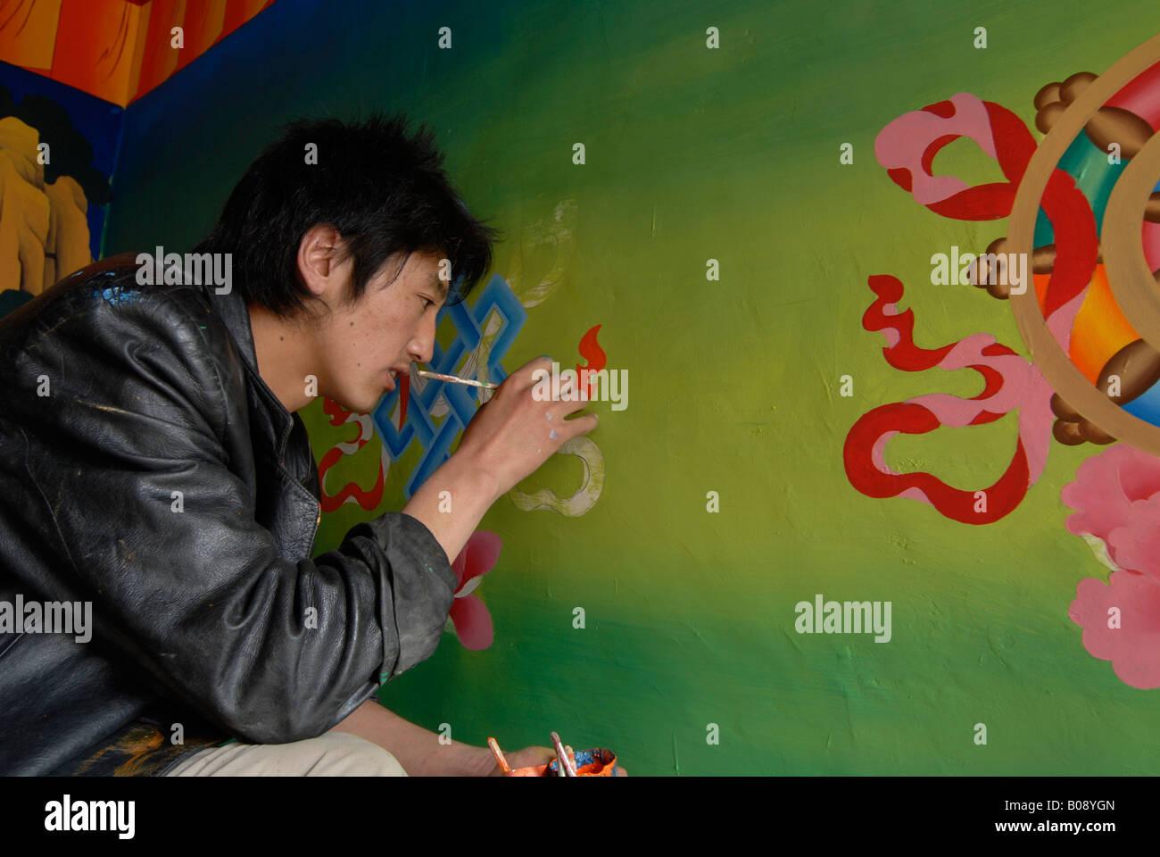 Tibetan artist painting eight auspicious symbols (Ashtamangala) onto a wall, Suntseling Monastery, Shangri-La County, - Stock Image