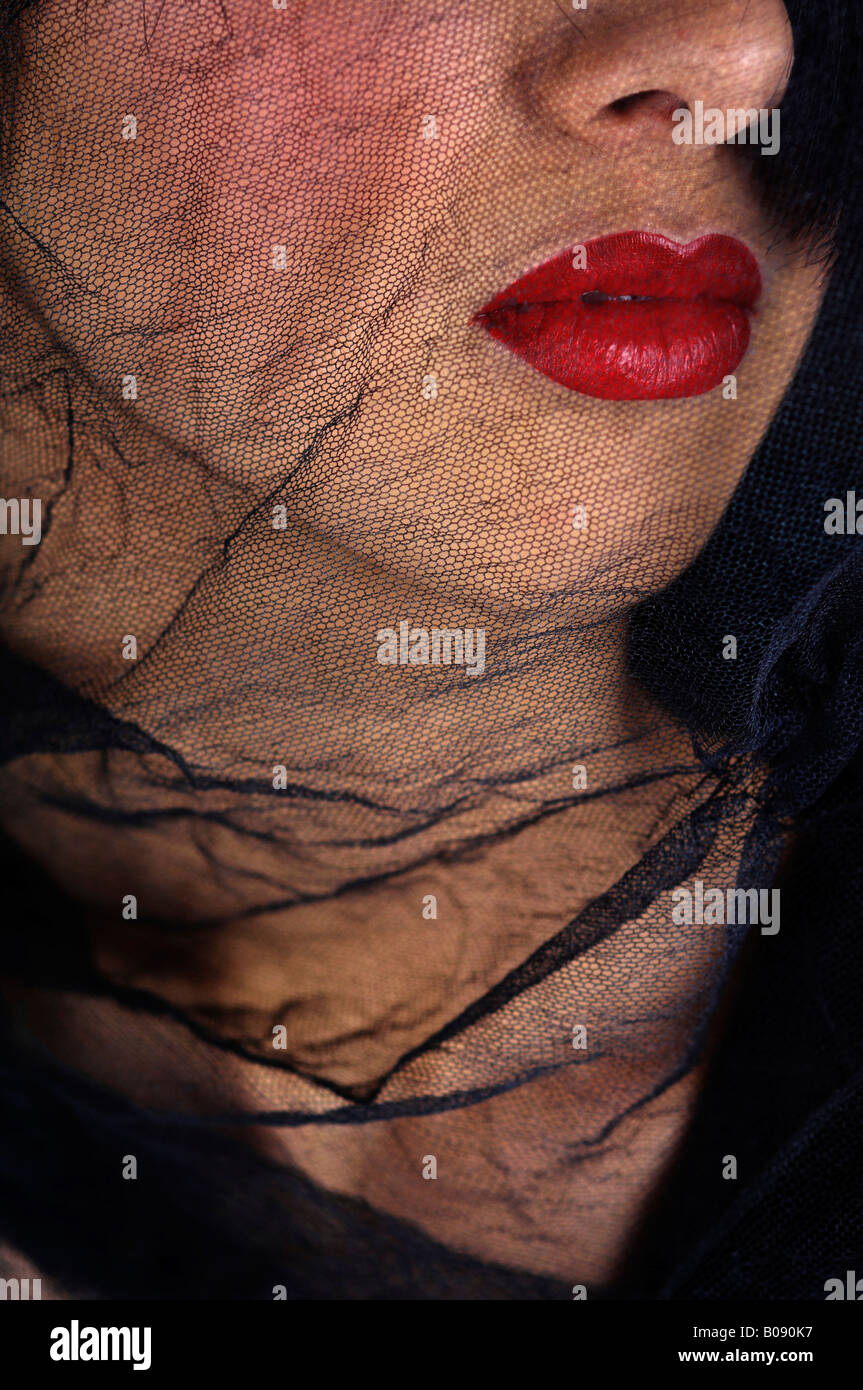 Netted black veil covering a woman's face, widow - Stock Image