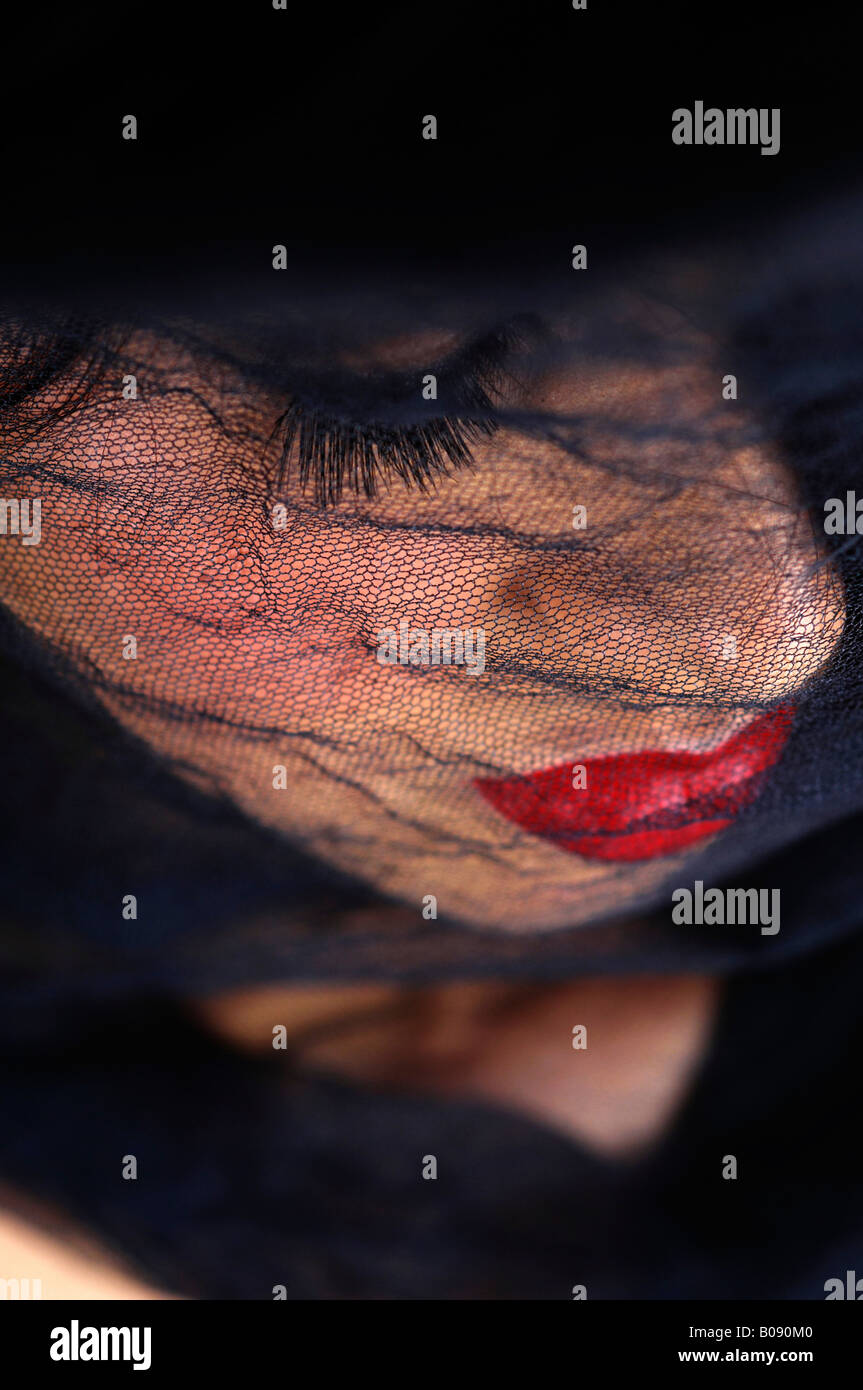 Netted black veil covering a young woman's face, widow - Stock Image