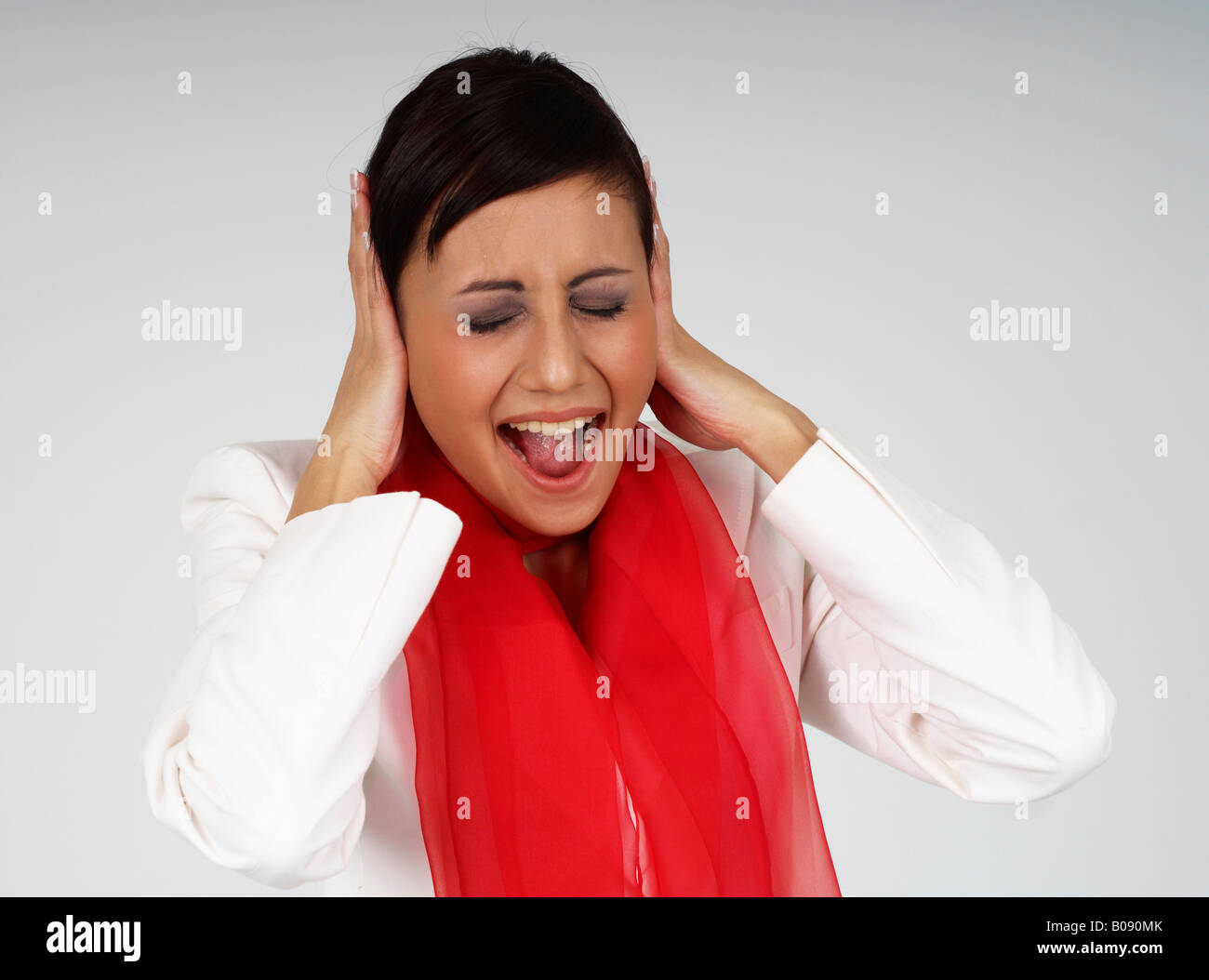 Young businesswoman shouting in desperation, frustrated - Stock Image