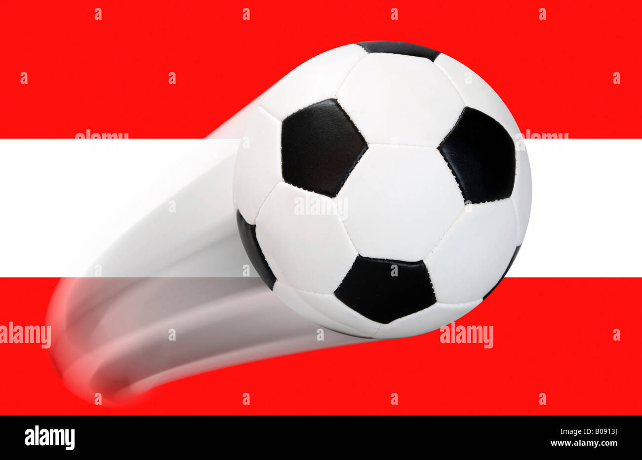 Football flying in front of an Austrian flag - series Stock Photo