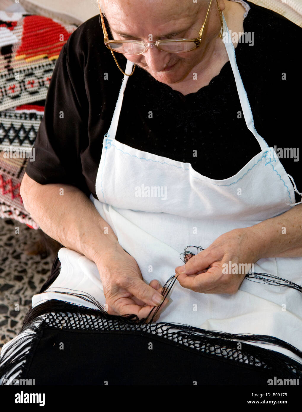 Old woman doing needlework, handmade rugs, Dorgali, Sardinia, Italy - Stock Image