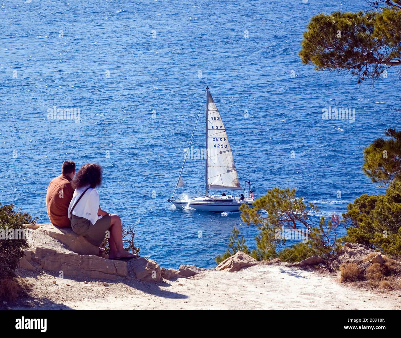 Couple sitting on the edge of a steep coast watching a sailboat near Sant Elm, Majorca, Balearic Islands, Spain Stock Photo