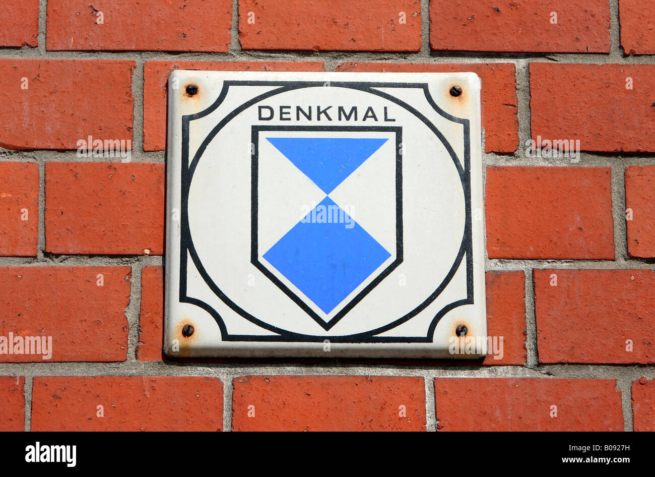 Plaque mounted on a brick wall marking an historic building, Germany - Stock Image