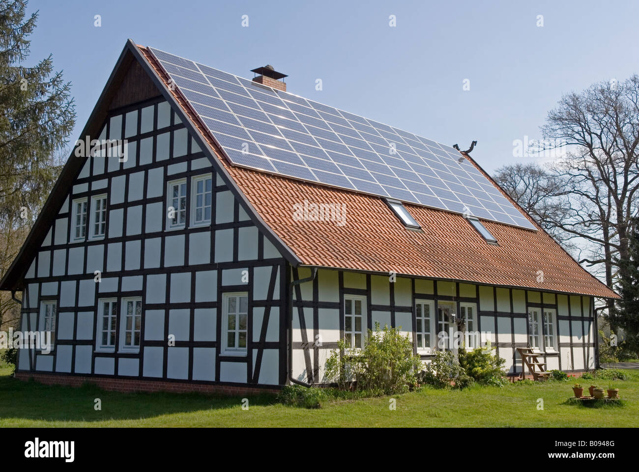 Traditional half-timber framed house with solar panels fitted to the roof, Strohen, Lower Saxony, Germany. - Stock Image