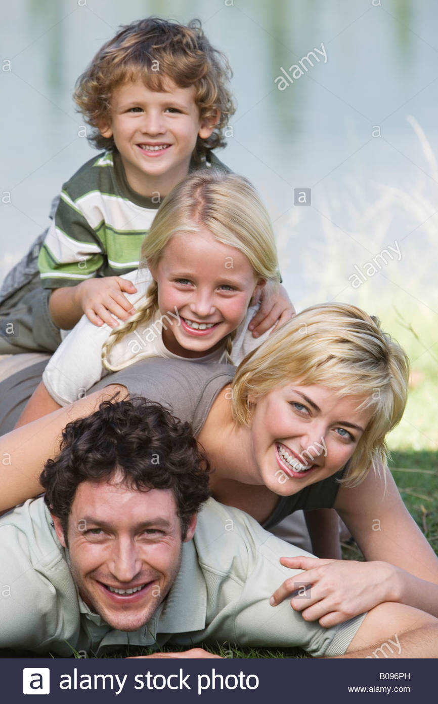 Family with two children lying on grass, human pyramid, in front of lake - Stock Image