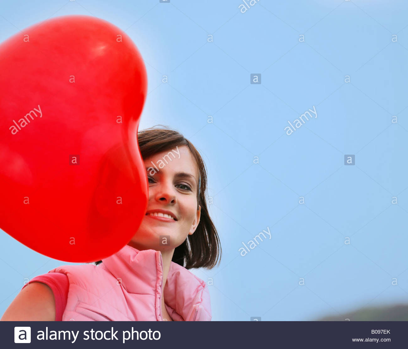 woman with red heart-shaped balloon - Stock Image
