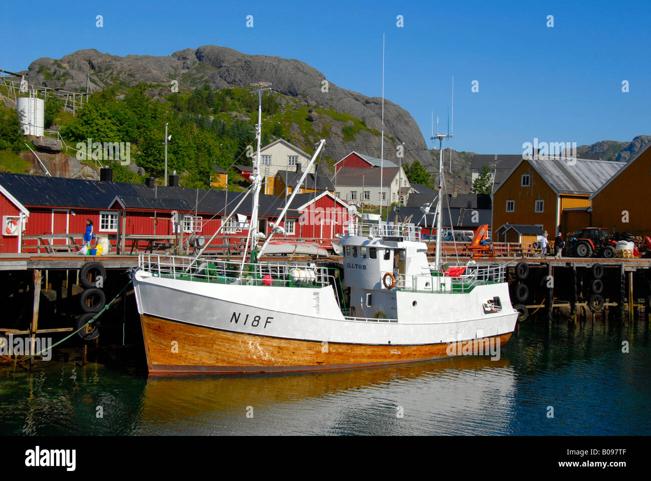 Wooden fishing boat tied up to a jetty and red wooden 'rorbu' houses in Nusfjord, Lofoten Archipelago, Norway, - Stock Image
