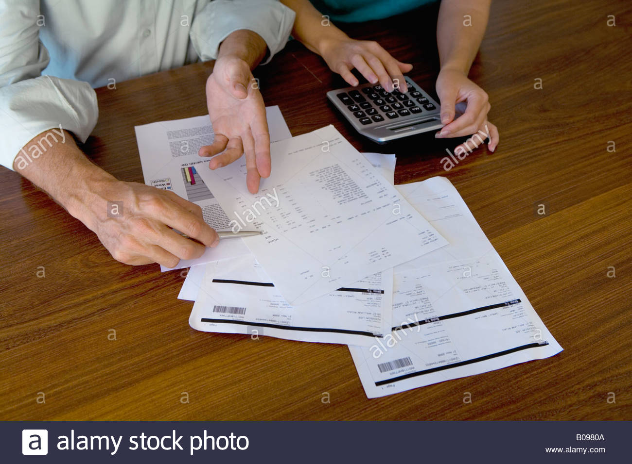 Mature couple looking at bills, using calculator, detail of hands - Stock Image