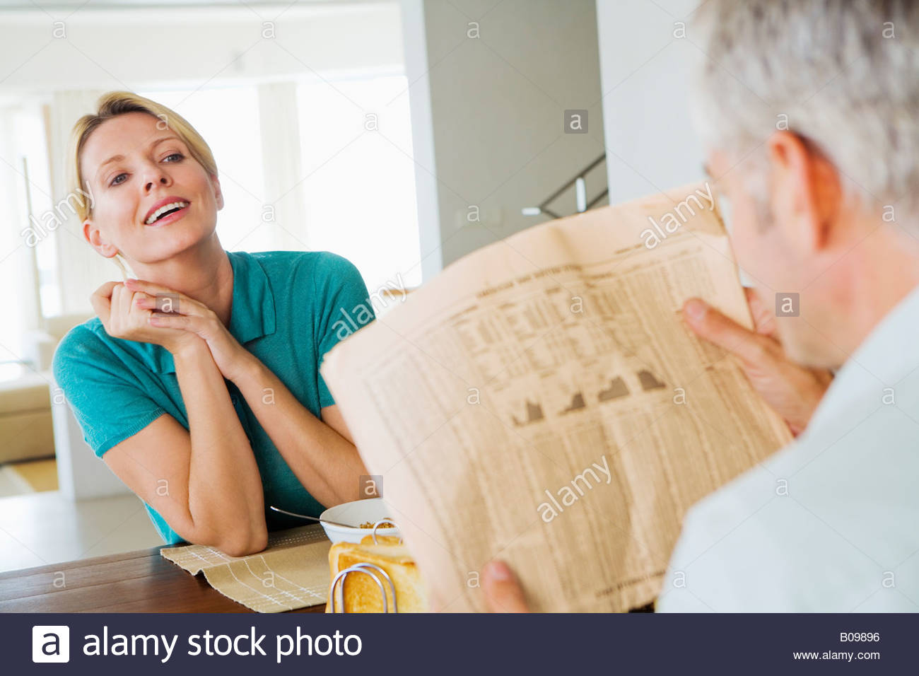 Mature couple at breakfast man reading financial newspaper - Stock Image