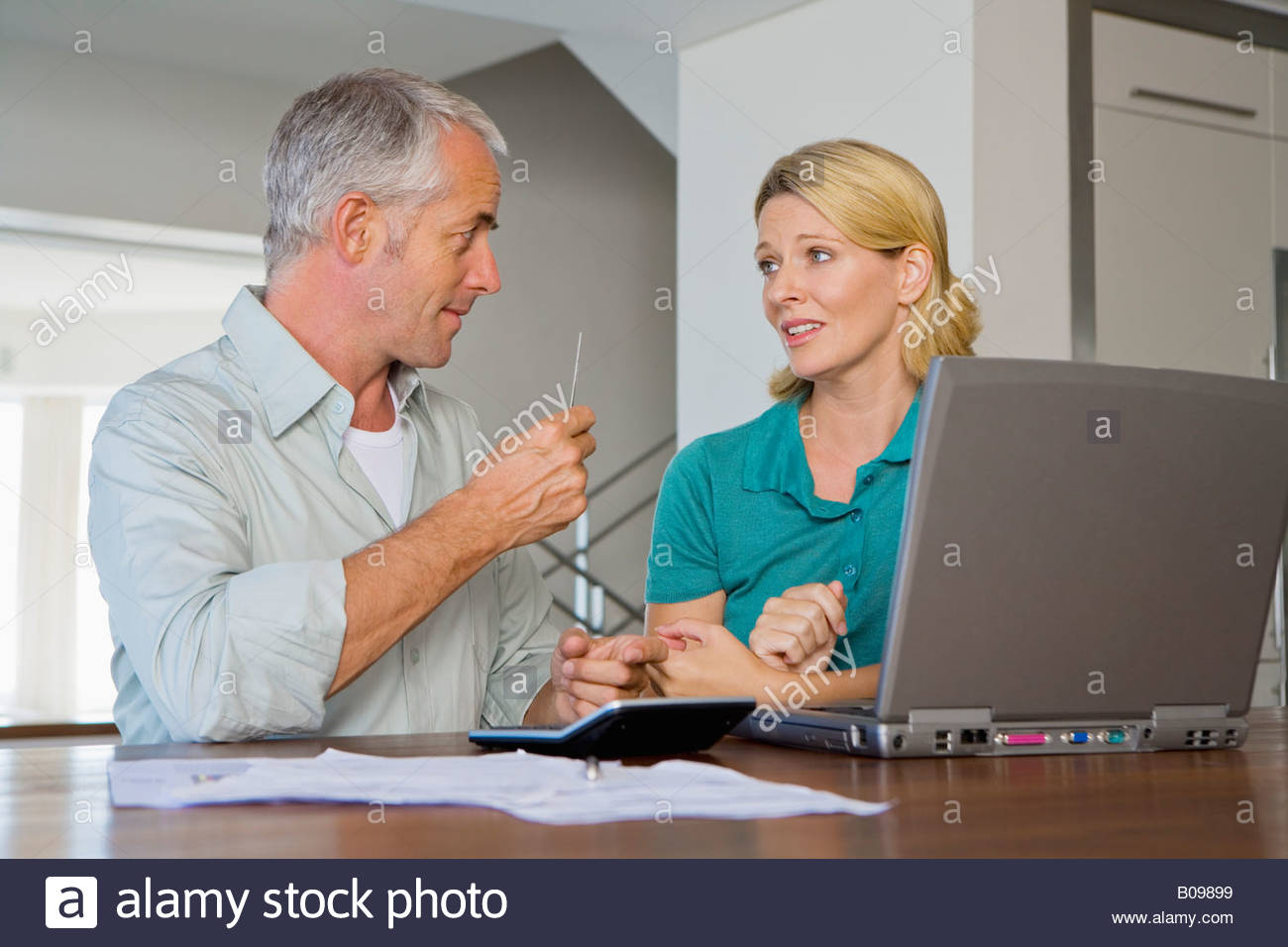 Mature couple arguing about financial situation, using calculator and Laptop - Stock Image