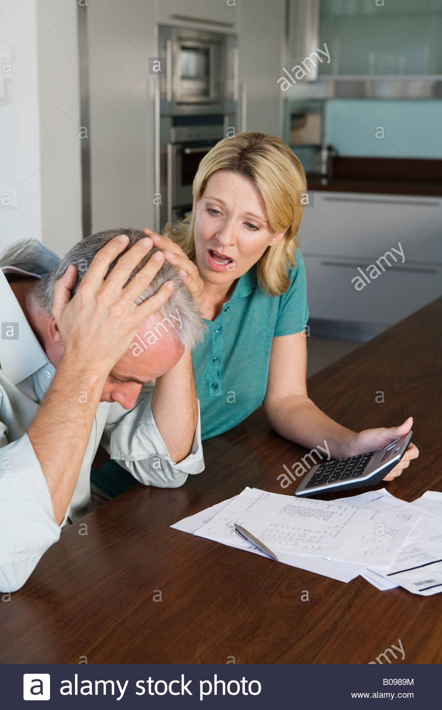 Mature couple stressed, looking at finance statement - Stock Image