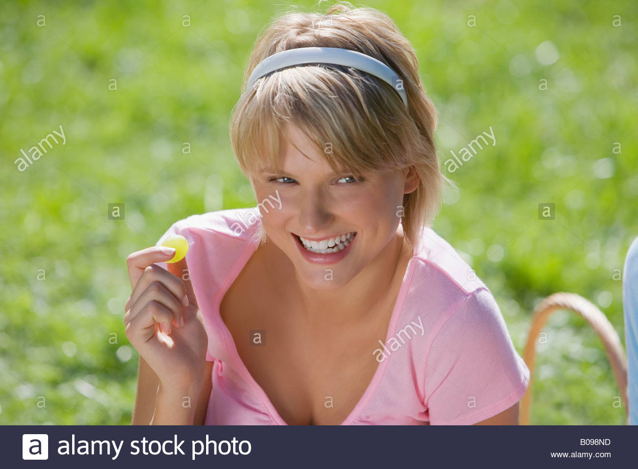Young woman having a picnic and eating a grape, portrait - Stock Image
