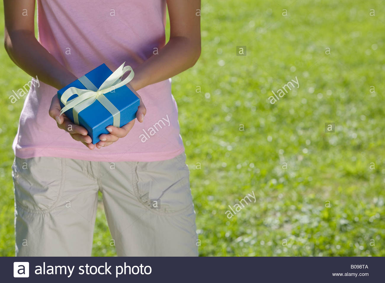 Young woman holding blue present with yellow ribbon in her hands - Stock Image