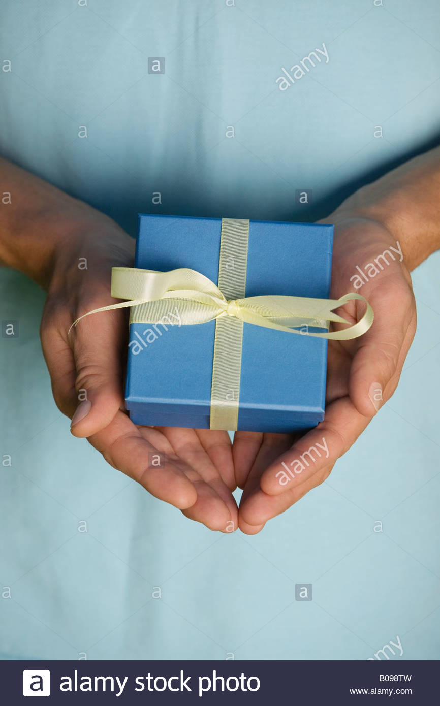 Man holding blue present tied with yellow ribbon in his hands - Stock Image