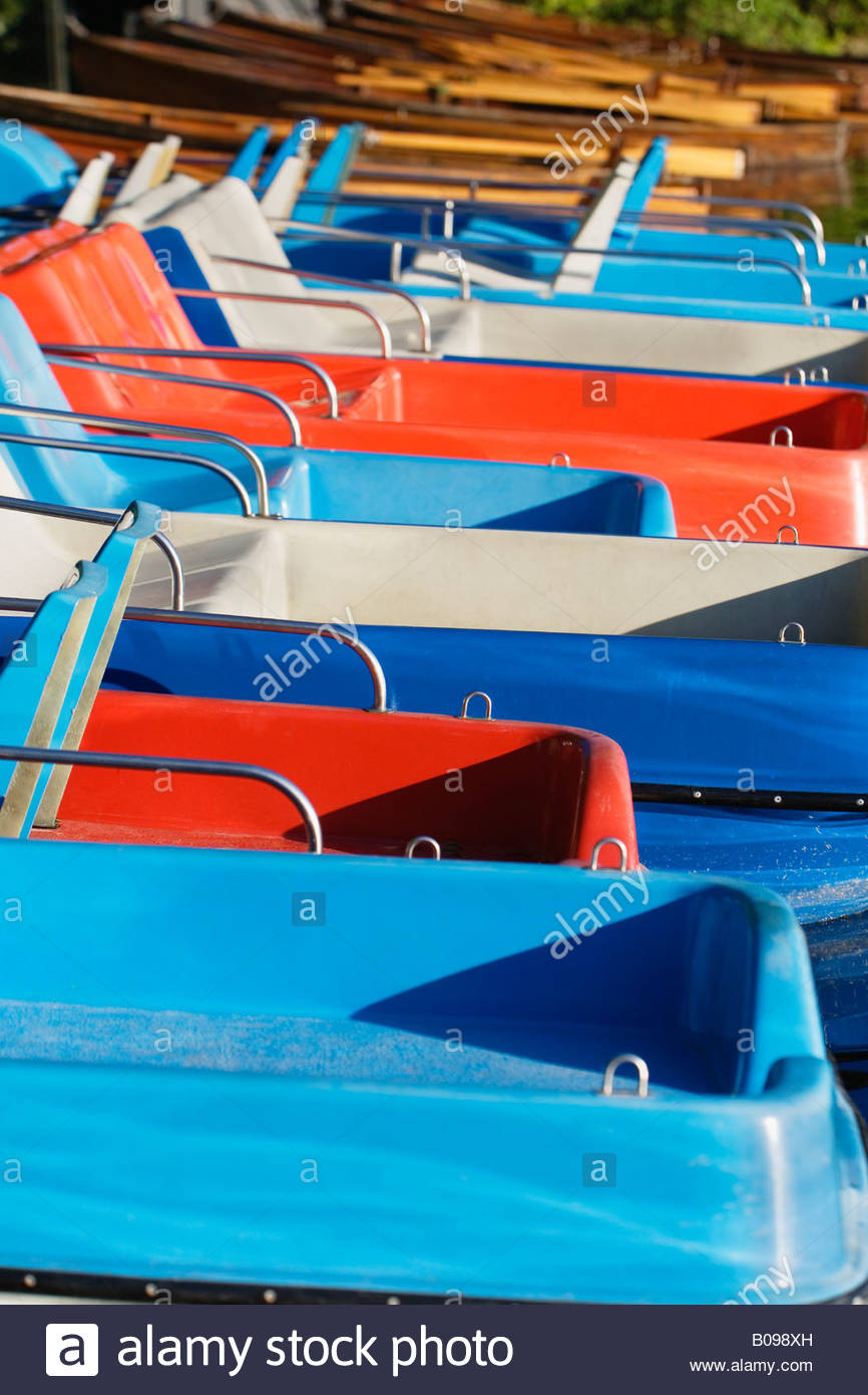 Row of paddel boats moored at side of Kleinhesseloher lake Munich, Germany - Stock Image