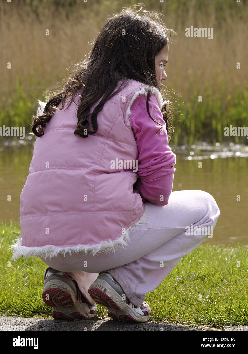 Young girl crouched down beside the river bank looking onto the water. - Stock Image